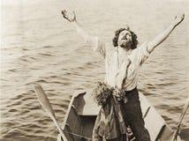 Homme et enfant échoués en mer Photo stock