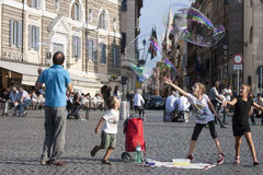 Homme et enfants avec de grandes bulles de savon images libres de droits