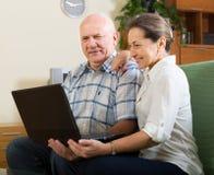 Homme et femme à l'aide de l'ordinateur portable à la maison Images stock