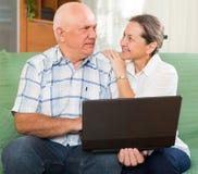 Homme et femme à l'aide de l'ordinateur portable à la maison Photos stock