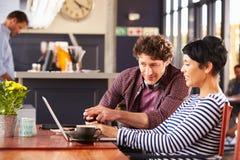 Homme et femme à l'aide de l'ordinateur portable à un café Photos stock
