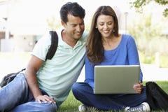 Homme et femme à l'aide de l'ordinateur portable dehors Image stock