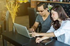 Homme et femme à l'aide de l'ordinateur portable en café Photo libre de droits