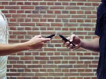 Homme et femme à l'aide des portables pour partager des fichiers Photographie stock libre de droits