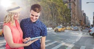 Homme et femme à la mode avec le comprimé contre la rue ensoleillée avec des fusées Image libre de droits