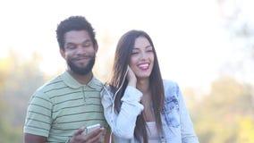 Homme et femme écoutant la musique ensemble, partageant des écouteurs banque de vidéos