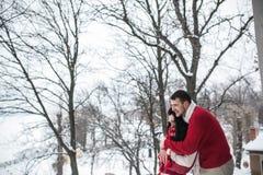 Homme et femme étreignant en parc couvert de neige Photos libres de droits