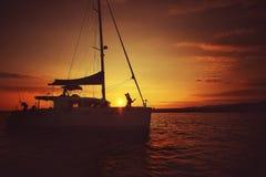 Homme et femme étreignant sur un yacht au coucher du soleil Images libres de droits