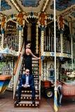 Homme et femme adultes sur un carrousel Photographie stock libre de droits