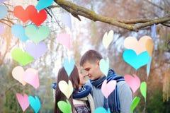 Homme et femme affectueux en parc avec le décor des coeurs Photo libre de droits