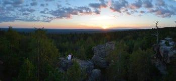 Homme et femme appréciant la vue de coucher du soleil de la grande roche en montagne, ville en pierre de nature Image stock