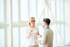 Homme et femme appréciant le café dans le bureau Image libre de droits