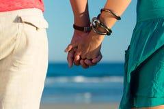 Homme et femme appréciant le coucher du soleil sur la plage Photo stock