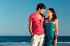 Homme et femme appréciant le coucher du soleil sur la plage Images libres de droits