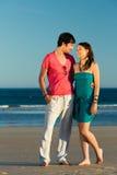 Homme et femme appréciant le coucher du soleil sur la plage Images stock