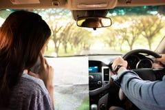 Homme et femme asiatiques employant le mobile sur le voyage par la route et les jeunes heureux Co photographie stock libre de droits