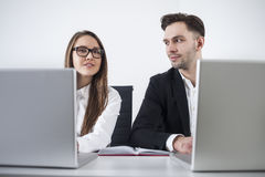 Homme et femme aux ordinateurs portables photos stock