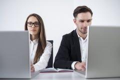 Homme et femme aux ordinateurs portables dans le bureau Images libres de droits