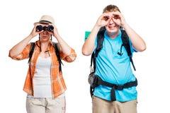 Homme et femme avec des jumelles, photo drôle sur un blanc Photographie stock libre de droits