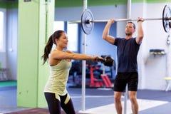 Homme et femme avec des poids s'exerçant dans le gymnase Images libres de droits