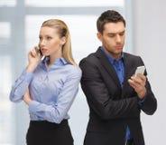 Homme et femme avec des téléphones portables Image stock