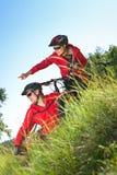 Homme et femme avec des vélos de montagne dans un pré Photo stock