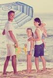 Homme et femme avec deux enfants se tenant ensemble sous l'umbrel de plage Photo stock