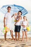 Homme et femme avec deux enfants se tenant ensemble sous l'umbrel de plage Image stock