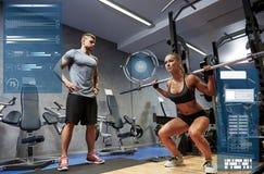 Homme et femme avec la barre fléchissant des muscles dans le gymnase photographie stock libre de droits
