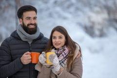 Homme et femme avec la boisson chaude sur la neige photos libres de droits