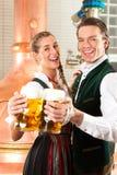 Homme et femme avec la glace de bière dans la brasserie Images libres de droits