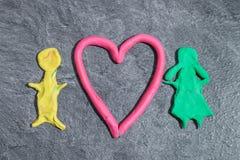 Homme et femme avec le coeur fait de pâte de jeu devant le fond gris Photo libre de droits