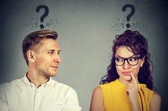 Homme et femme avec le point d'interrogation regardant l'un l'autre avec l'intérêt Images stock