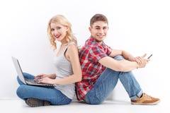 Homme et femme avec le téléphone portable, ordinateur portable Images libres de droits