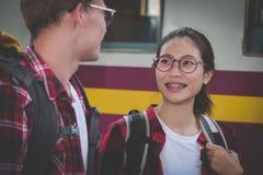 Homme et femme avec le train de attente de sac à dos à la gare ferroviaire photos libres de droits