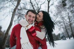 Homme et femme ayant l'amusement dans le parc couvert de neige Image libre de droits