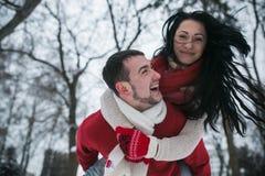 Homme et femme ayant l'amusement dans le parc couvert de neige Image stock