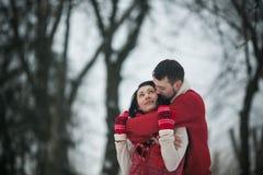Homme et femme ayant l'amusement dans le parc couvert de neige Photo libre de droits
