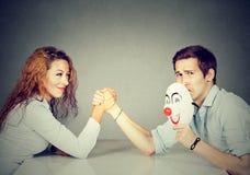 Homme et femme ayant le bras de fer image stock
