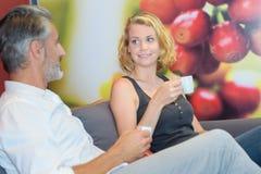 Homme et femme ayant le café de tasse Photo stock