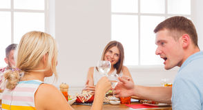 Homme et femme blonde à la table de dîner, partie pour des amis Photographie stock