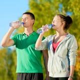 Homme et femme buvant de la bouteille Photographie stock libre de droits