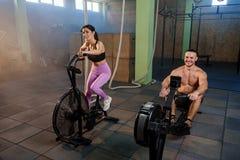 Homme et femme caucasiens de sport pendant la formation dans le gymnase photographie stock
