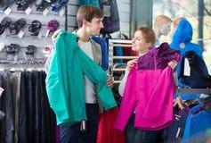 Homme et femme choisissant l'habillement de sport Photographie stock