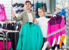 Homme et femme choisissant l'habillement de sport Photo stock