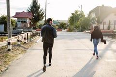 Homme et femme courant au croisement de chemin de fer Image stock