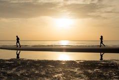Homme et femme courant ensemble sur la plage dans le coucher du soleil - lever de soleil Photos stock