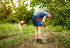 Homme et femme, creusant et pellant dans le printemps de jardin photos libres de droits