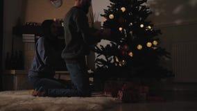 Homme et femme décorant l'arbre de Noël à la maison Les couples heureux se préparent à la fête de Noël dans la chambre noire Conc banque de vidéos