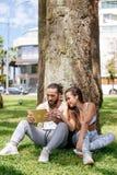 Homme et femme détendant avec le comprimé numérique en parc après la formation de sports images libres de droits